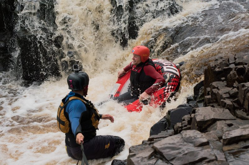 Participant going off the waterfall in their white water tube